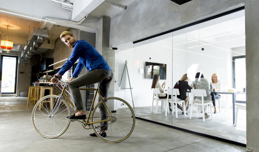 Joven en una bicicleta en una oficina moderna